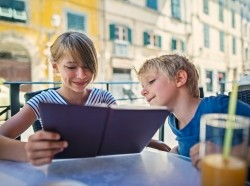 A young girl and boy look at a restaurant menu