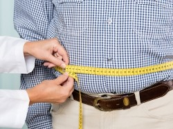 Doctor measuring a man's stomach with measuring tape