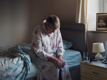 Middle-aged woman in pain sitting on her bed