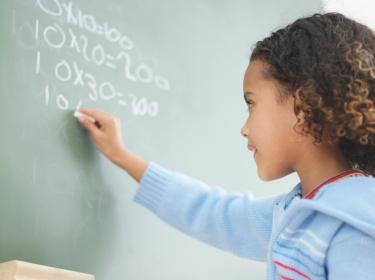 Girl doing multiplication on a chalkboard