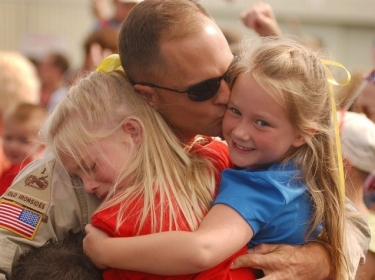 Veteran returning home hugging his daughters