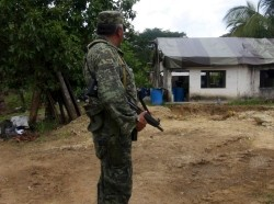 A soldier keeps watch outside a house being used as a meth lab in the community of San Juan Mazatlan, Mexico