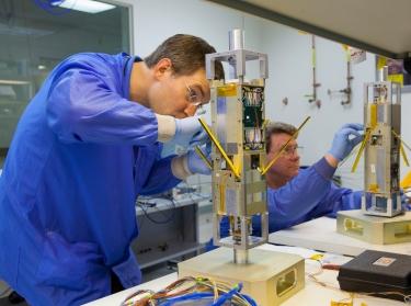 Technicians assemble a small satellite