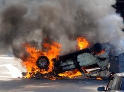 A burning car upside down on a street