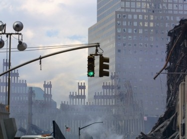 The World Trade Center site at Ground Zero, debris and vehicles seen spread around the area already 2 weeks after the September 11, 2001 disaster. Fires are still burning underground and smoke and haze fills the sky