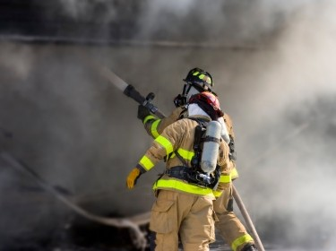 Two firefighters holding a hose and surrounded by smoke