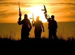 Three people stand holding guns silhouetted against a sunset