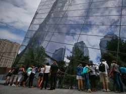 Visitors to the 911 Memorial plaza peer through glass windows into the 911 Memorial Museum at the World Trade Center site in New York