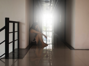 A woman sitting alone in a corridor resting her head in her hand
