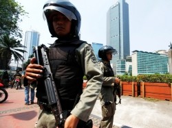 Indonesian anti-terror policemen hold their rifle as they stand guard at the business district in Jakarta, September 11, 2011