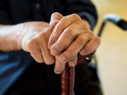 elderly person's hands on walking cane