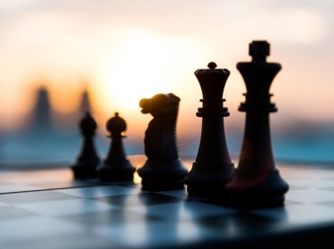 Chess pieces on a chess board against a sunset