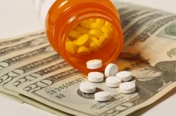 Pill bottle and pills on top of money