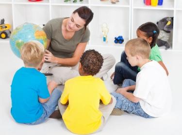 teacher showing globe to children