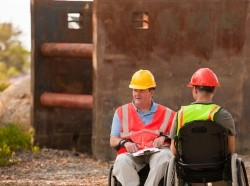 Two men onsite wearing hard hats in wheelchairs