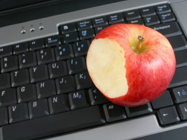 red apple and laptop keyboard