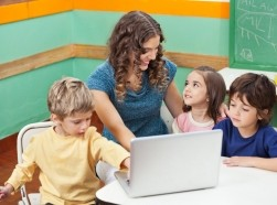 preschool teacher with students around a laptop