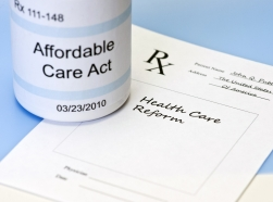 A prescription bottle labeled Affordable Care Act and prescription pad