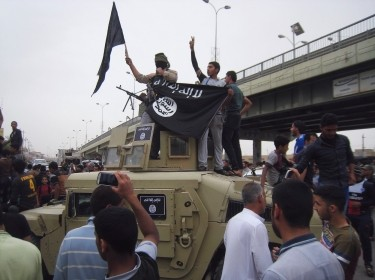Al-Qaeda fighters celebrate on vehicles taken from Iraqi security forces, on a m