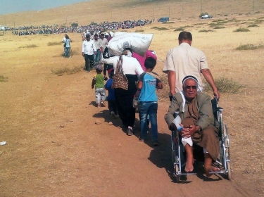 Kurdish men, women, and children fleeing Syria to seek protection by the Turkish