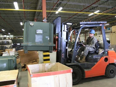 A soldier pulls a vehicle engine from storage