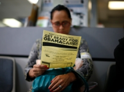 An attendee at a health insurance enrollment event in Cudahy, California reads a leaflet, March 27, 2014