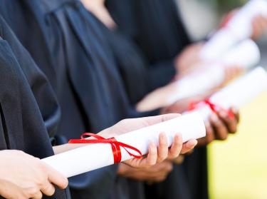 Graduates holding diplomas.