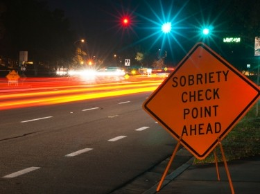 Sobriety checkpoint sign on the side of a busy highway at night