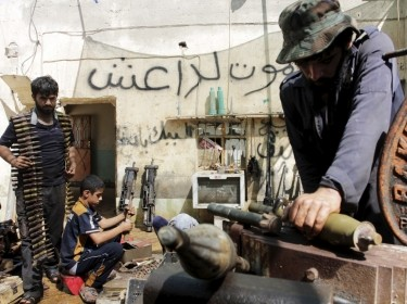 Iraqi volunteers fix weapons for the Hashid Shaabi militia at a shop on the outskirts of Basra, June 16, 2015