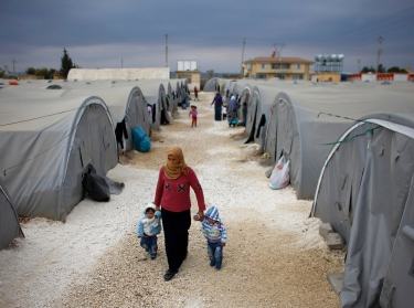 A Kurdish refugee woman from Syria walks with her children at a refugee camp in Suruc, Turkey, November 17, 2014