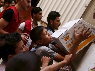 Boys help members of the Syrian Arab Red Crescent unload parcels of medical and humanitarian aid in Damascus, Syria, July 23, 2015