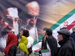 People pass a large picture of Iran's Supreme Leader Ayatollah Khamenei and the late leader of the Islamic Revolution Ayatollah Khomeini during a ceremony marking the 37th anniversary of the Islamic Revolution, in Tehran, February 11, 2016