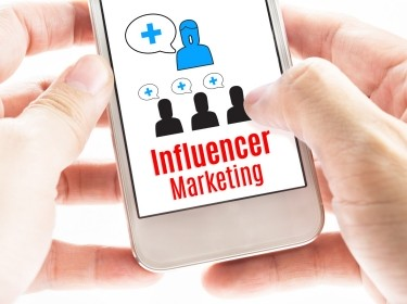 Person holding a smartphone displaying influencer marketing