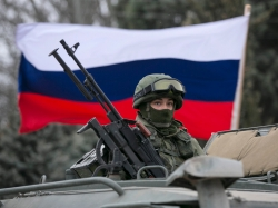 A Russian soldier on top of an army vehicle keeps watch outside a border guard post in the Crimean town of Balaclava, March 1, 2014