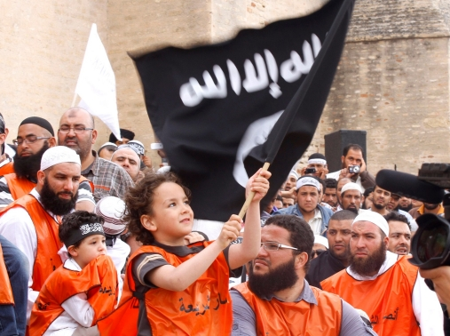 A young boy waves a black flag inscribed with Islamic verses at a rally of Tunisian Salafi Islamists in the central town of Kairouan, May 20, 2012
