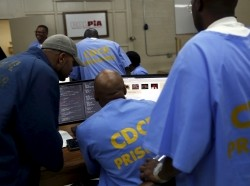 Prisoners gather around a computer following a graduation ceremony from a computer coding program at San Quentin State Prison in San Quentin, California April 20, 2015