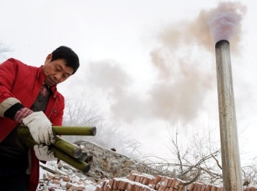 A Chinese meteorological department worker burns catalyst for cloud seeding and snowmaking to end drought in Beijing, China, February 17, 2009, photo by Oriental Image via Reuters