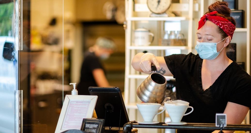 A barista making coffee while wearing a mask, photo by stockstudioX/Getty Images