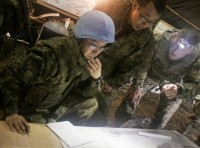 Members of the Japan Ground Self-Defense Force and a U.S. Army captain examine a field artillery safety diagram at Yausubetsu Training Area, Japan, photo by U.S. Army