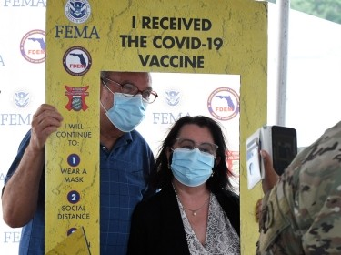 People pose for a photo after being vaccinated at the FEMA-supported COVID-19 vaccination site at Valencia State College in Orlando, Florida, photo by Paul Hennessy/SOPA Images/Sipa USA/Reuters