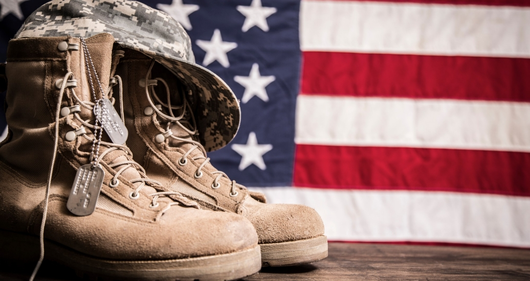 USA military boots, hat and dog tags with American flag in background. Photo by fstop123/Getty Images