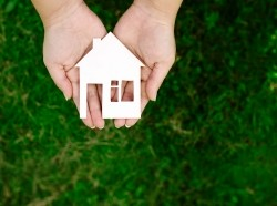 Hands holding a cut-out of a house over a background of grass. Photo by zahar2000 / Adobe Stock