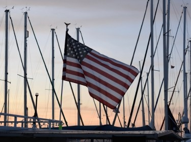 An American flag waving at sunset, photo by Emily Sisson/Getty Images