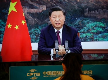 A journalist sits next to a screen showing Chinese President Xi Jinping delivering a speech via video for the opening ceremony of the 2020 China International Fair for Trade in Services (CIFTIS), at a media centre in Beijing, China September 4, 2020, photo by Tingshu Wang/Reuters