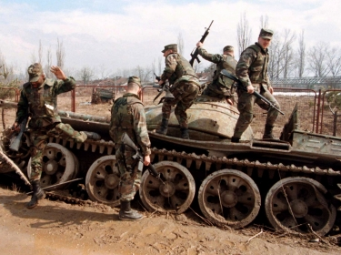 A group of U.S. NATO Implementation Force (IFOR) soldiers climb off a destroyed Bosnian tank March 16, 1996, that was hit in 1992, at the beginning of the war between Bosnian Moslem and Serbs, photo by Peter Andrews/Reuters