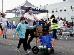 A family pushes a cart after receiving groceries during a Mother's Day food distribution event organized, Los Angeles, California, May 9, 2020, photo by Patrick T. Fallon/Reuters