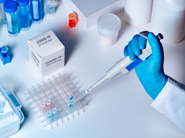 Scientist working with a diagnostics kit to detect the virus that causes COVID-19, photo by anyaivanova/Getty Images