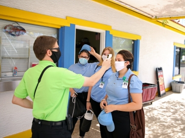 The front gate admissions supervisor checks employees' temperatures before the start of their shifts at Golfland Sunsplash water park in Mesa, Arizona, May 15, 2020, photo by Caitlin O'Hara/Reuters