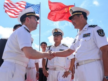 Capt. James T. Jones, commanding officer of the USS Shiloh, greets Rear Adm. Zhang Wendan of the Chinese People's Liberation Army Navy
