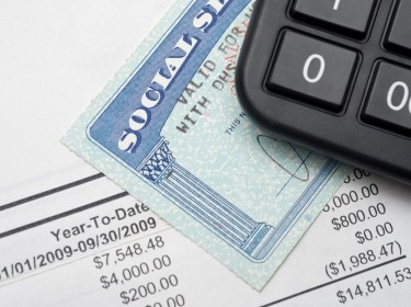 A calculator, social security card and financial document.